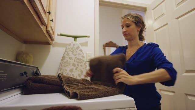 stockvideo's en b-roll-footage met een jonge vrouw in de jaren dertig plooien handdoeken in een woonkamer wasruimte - vrouw schoonmaken