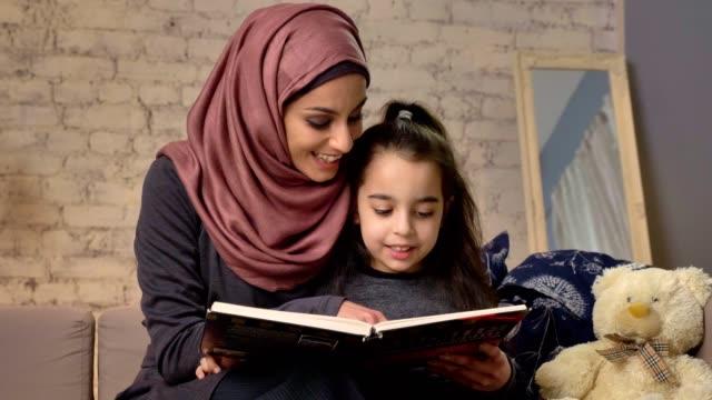 ung kvinna i hijab sitter på soffan med dottern och lär henne hur till läsa, bok, lycklig familj konceptet 50 fps - hijab bildbanksvideor och videomaterial från bakom kulisserna