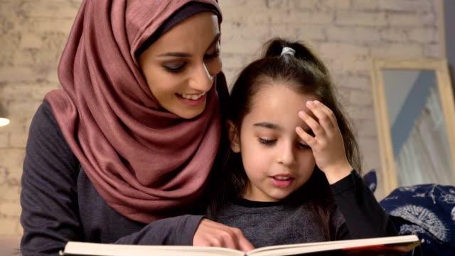 ung kvinna i hijab sitter på soffan med dottern och hennes lär för att läsa, bok, lycklig familj koncept, närbild 50 fps - hijab bildbanksvideor och videomaterial från bakom kulisserna