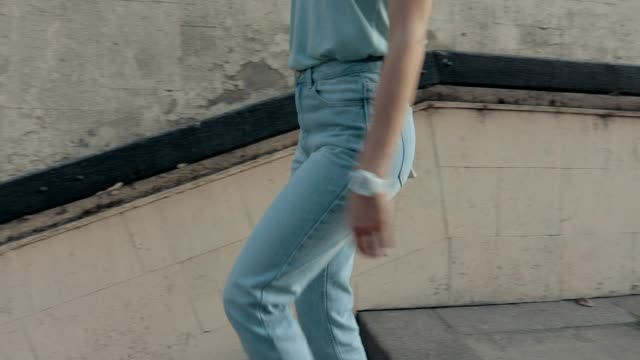Young woman in jeans and a T-shirt is walking around the city in summer, slow motion video