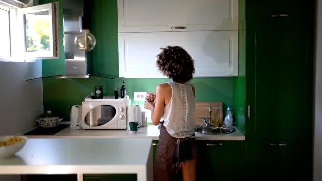 ung kvinna i köket - looking inside inside cabinet bildbanksvideor och videomaterial från bakom kulisserna