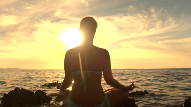 CLOSE UP: Young woman in lotus yoga position by the ocean on magical evening