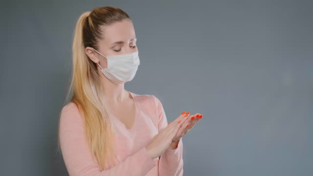 young woman in mask sprays antiseptic on hand and rubs