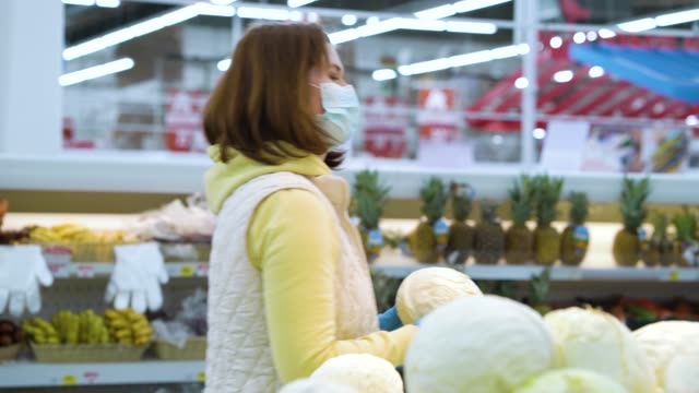 Young woman in medical mask and gloves buying cabbage in supermarket video