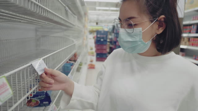 Young Woman in Medical Mask Shopping During Empty Shelf Young asian woman wearing mask and reading label on empty shelf in Supermarket in Bangkok, Thailand. market retail space stock videos & royalty-free footage