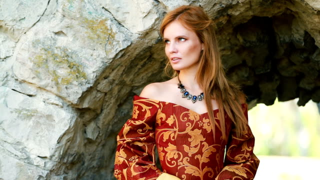 Young woman in medieval dress in front of stone wall Young woman in medieval dress in front of stone wall on the wind princess stock videos & royalty-free footage