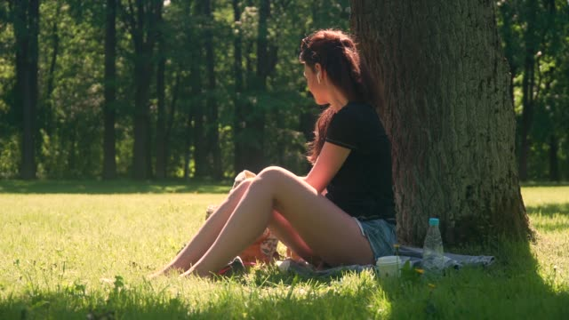 young woman in park uses smartphone and tablet - cuffie wireless video stock e b–roll