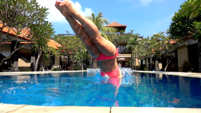 SLOW MOTION Young woman in pink bikini jumping head first into luxury pool water
