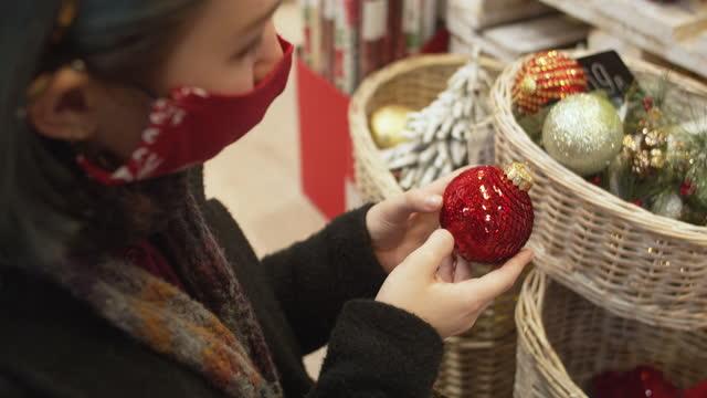 vídeos de stock e filmes b-roll de young woman in protective face mask on christmas shopping during covid-19 - objeto decorativo