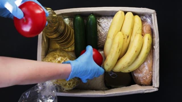 vídeos y material grabado en eventos de stock de una joven con guantes protectores llena una caja con comida. la caja para donaciones de alimentos. entrega de alimentos. - food drive