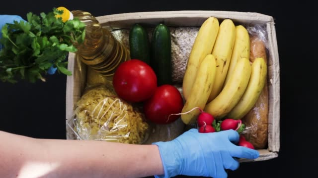 A young woman in protective gloves fills a box with food. The box for donations of food. Food delivery. A young woman in protective gloves fills a box with food. The box for donations of food. Food delivery. food drive stock videos & royalty-free footage