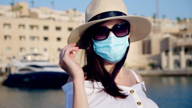 stockvideo's en b-roll-footage met jonge vrouw in beschermend masker, de zomerkleren, zonnebril en zonnehoed, op de achtergrond van een jacht in jachthaven. yachting seizoen is open, reizen na covid-19 - cruise