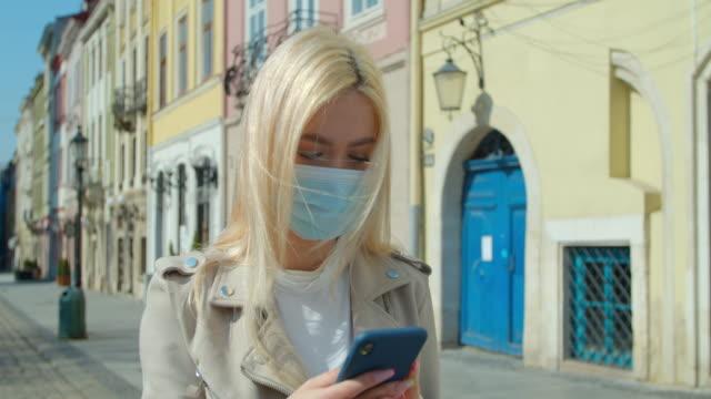 junge frau in schutzmaske mit smartphone in der straße der altstadt. besorgte mädchen suchen nachrichten über covid-19. pandemie covid-19 coronavirus-schutz. - smartphone mit corona app stock-videos und b-roll-filmmaterial
