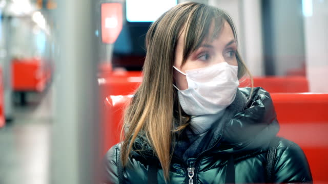 Young woman in protective medical face mask in a subway car Young woman in protective medical face mask in a subway car, pandemic coronavirus concept bus stock videos & royalty-free footage