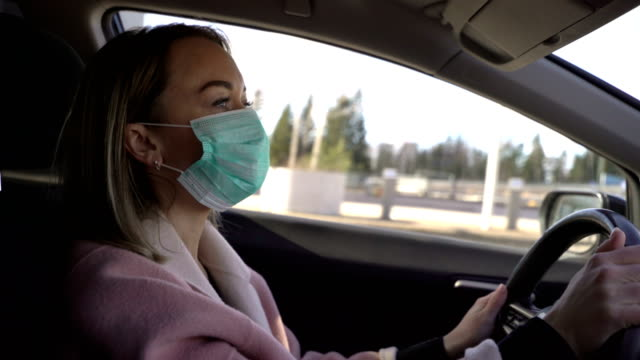 Video Young woman in protective sterile medical face mask in a car,