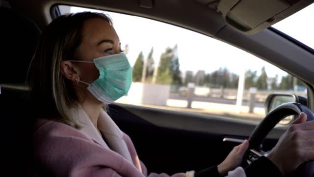ung kvinna i skyddande steril medicinsk ansiktsmask i en bil, - face mask bildbanksvideor och videomaterial från bakom kulisserna