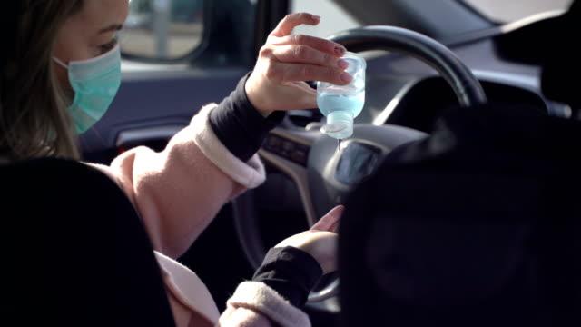 vídeos y material grabado en eventos de stock de mujer joven con mascarilla protectora de la cara estéril utiliza líquido desinfectante de manos en un coche - hand sanitizer