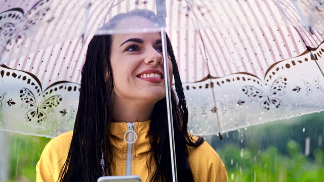SLO MO Young woman in raincoat using her smartphone in the rain