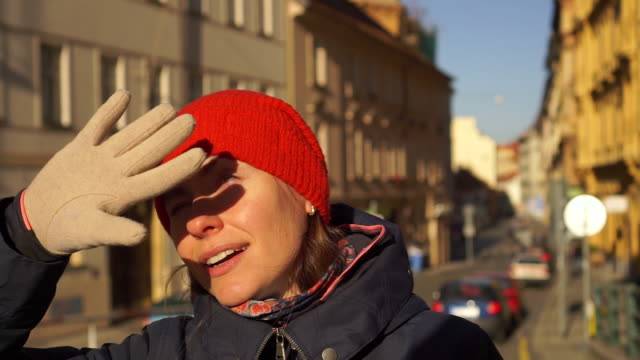 Young woman in red hat squinting from the bright winter sun on European old street