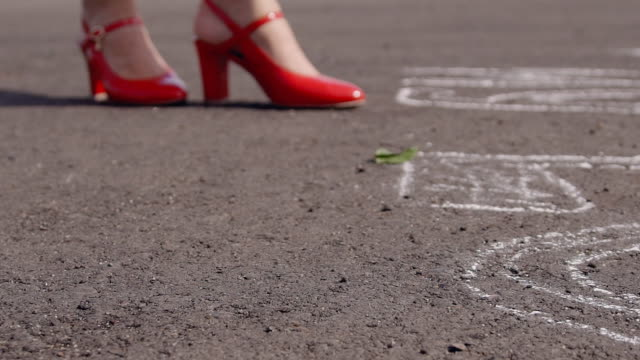 Young woman in red shoes stands on asphalt and drops scarlet rose video