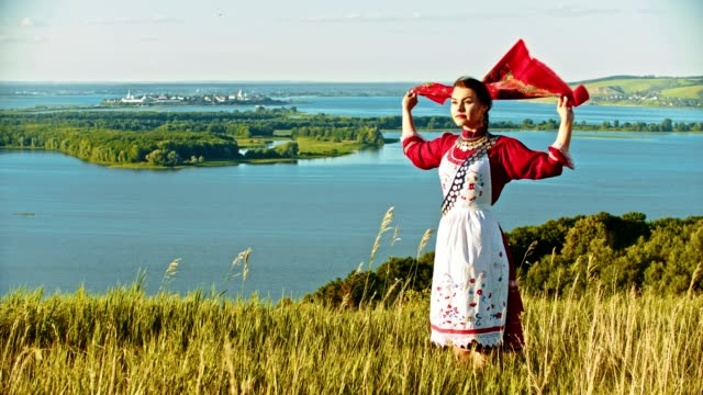 a young woman in russian folk clothes standing on the field and looking at the river - handkerchief flutters by the wind. - славянская культура стоковые видео и кадры b-roll