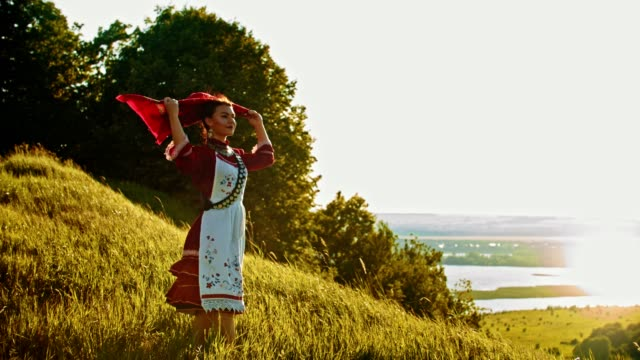 a young woman in russian folk clothes standing on the field and enjoying the view - putting a handkerchief on her head. - славянская культура стоковые видео и кадры b-roll