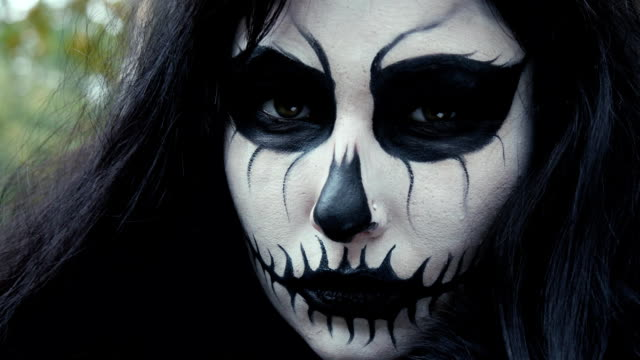 young woman in scary black and white halloween make up looking into camera - zucca legenaria video stock e b–roll