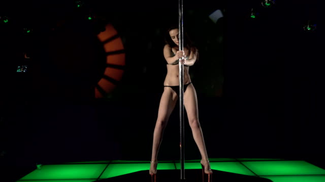 Young woman in sexy lingerie performs pole dance on nightclub lighted stage video