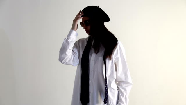 A Young woman in shirt, sunglasses and beret posing on the white background video