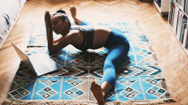 Young woman in sports clothing doing the splits while exercising at home Young Caucasian woman doing yoga at home. Enjoying and learning exercise from tutorials on her laptop. Practicing meditation and breathing exercise at home. doing the splits stock videos & royalty-free footage