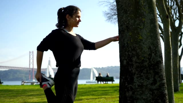Young woman in sportswear stretching in park Young woman in sportswear stretching in park. Side view of beautiful sporty girl leaning at tree and stretching leg at sunny day, handheld shot. Workout concept leaning stock videos & royalty-free footage