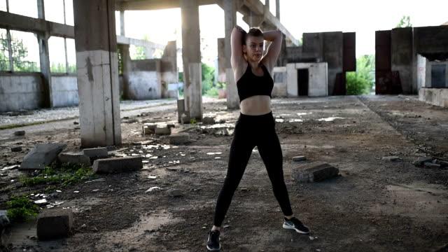 young woman in sportswear training on open air. - ludzka kończyna filmów i materiałów b-roll
