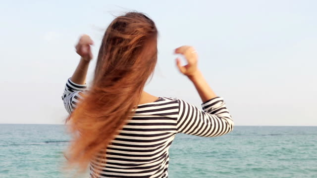 young woman in striped t-shirt straightens the hair on the beach, view from the back, slow motion - spettinato video stock e b–roll