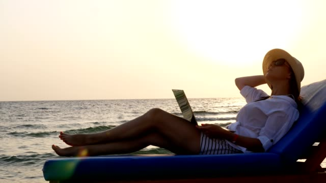 young woman in sunglasses and sun hat, uses laptop, lying on a lounger, on the beach by the sea, at sunset or sunrise. freelancer, remote work. summer vacation at sea video