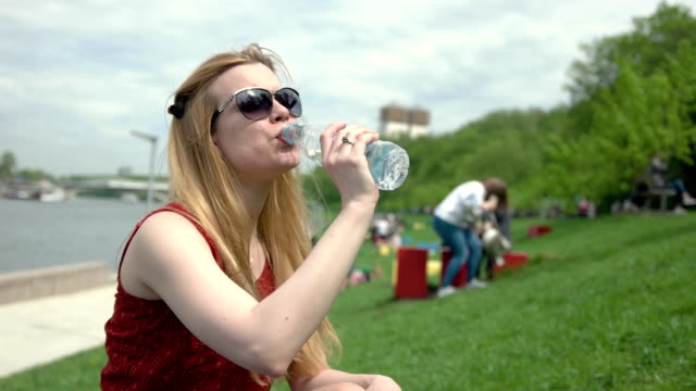young woman in sunglasses drinks water from a plastic bottle on summer day - femminilità video stock e b–roll