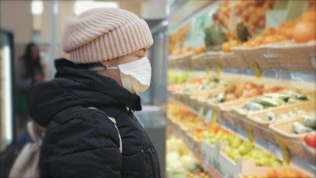 Young woman in supermarket in medical mask looks chooses and takes fruits. Coronavirus pandemic Covid-19 virus video