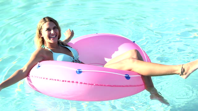 Young woman in swimming pool on inflatable ring video