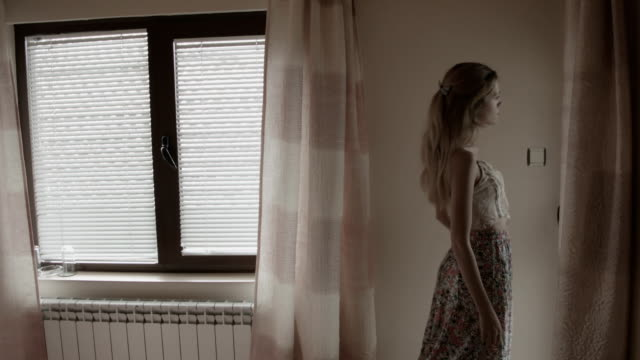 Young woman in the bedroom Woman looks out the window and lay down on the double bed. double bed stock videos & royalty-free footage