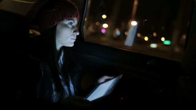 Young woman in the car using the tablet. video