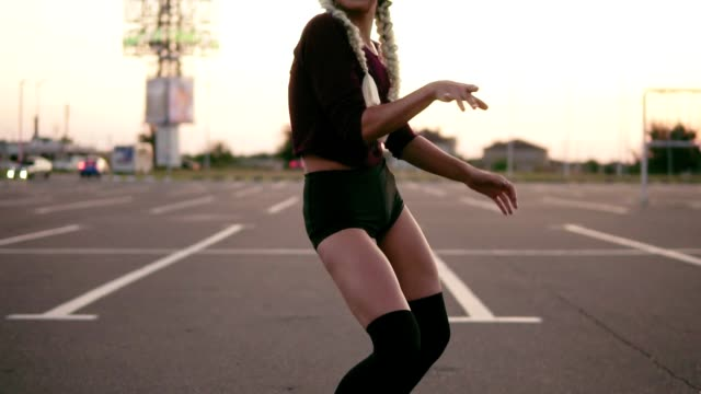 young woman in the crop top and shorts dance twerk on the parking during sunset in summertime. sexy moves. slowmotion shot - seduzione video stock e b–roll