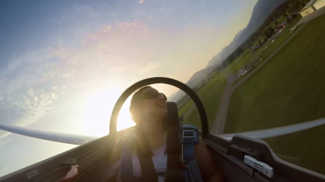 LD Young woman in the passenger seat of the glider enjoying the plane gliding low at sunset