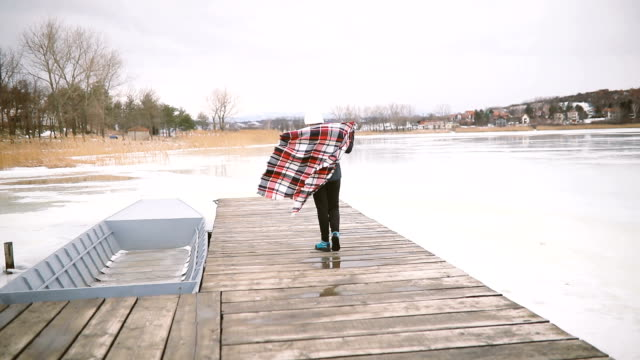 young woman in the snow wearing a checkered blanket - trekking sul ghiaccio video stock e b–roll