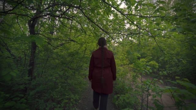 ung kvinna i promenader i grön vårskog och vänder sig till kameran, bakifrån - människorygg bildbanksvideor och videomaterial från bakom kulisserna
