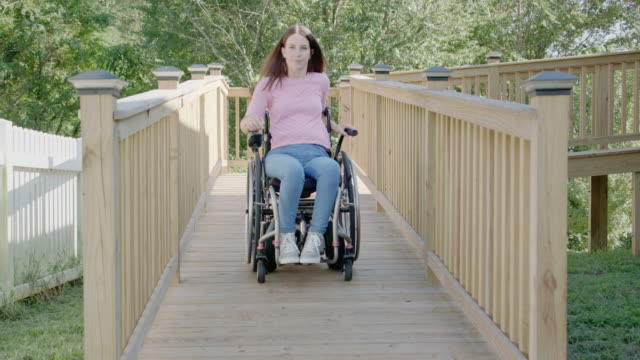 Young Woman in Wheelchair goes Down Wheelchair Ramp video