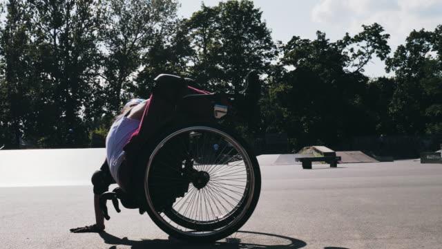 vídeos y material grabado en eventos de stock de joven en silla de ruedas en el parque de patinaje haciendo acrobacias y ruedas - deportes en silla de ruedas