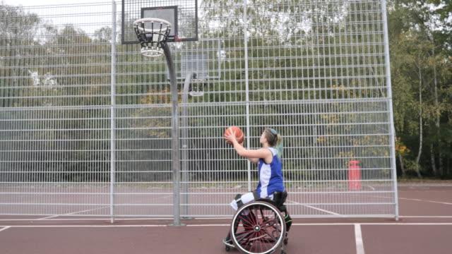 バスケットボールをしている車椅子の若い女性 - 障害スポーツとレクリエーション - 車椅子スポーツ点の映像素材/bロール