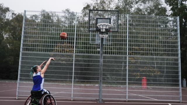 ung kvinna i rullstol spela basket-handikappidrott och rekreation - femininitet bildbanksvideor och videomaterial från bakom kulisserna