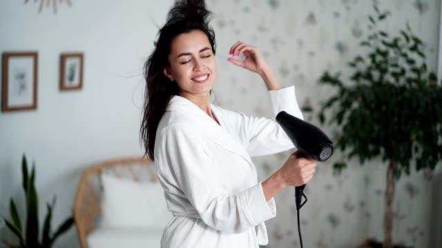 vidéos et rushes de jeune femme dans les danses blanches de peignoir et sèche des cheveux avec le sèche-cheveux - soins capillaires