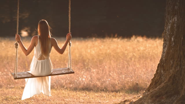 SLO MO TD Young woman in white dress swinging under a big tree video