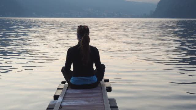 Young woman in yoga pose at the end of dock on lake meditating with view of mountains